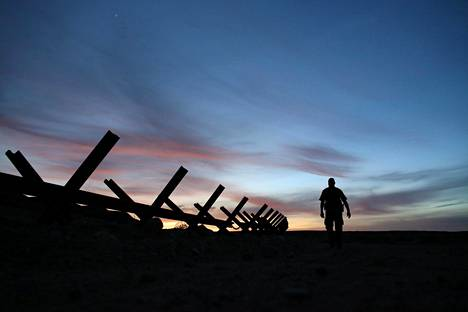 Yhdysvaltalainen rajavartia kävelee torstaina raja-aidan viertä Calexicon lähistöllä Kaliforniassa.