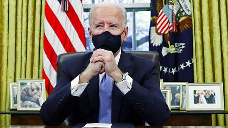Yhdysvaltain presidentti Joe Biden kuvattiin keskiviikkona Valkoisen talon työhuoneessaan, missä hän allekirjoitti ensi töikseen joukon presidentin asetuksia.