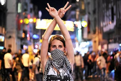 Hallitusta vastustava mielenosoittaja näytti voitonmerkkiä mellakkapoliisille Taksim-aukiolla Istanbulissa 22. kesäkuuta.
