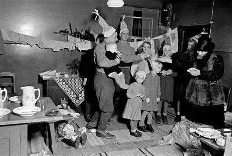 Tummiin pukeutunut joulupukki jakoi lahjoja helsinkiläiskodissa vuonna 1946.