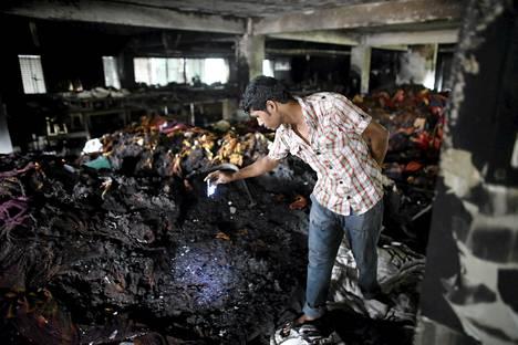 Työntekijä kävi läpi tulipalon aiheuttamia tuhoja vaatetehtaalla Bangladeshissa.
