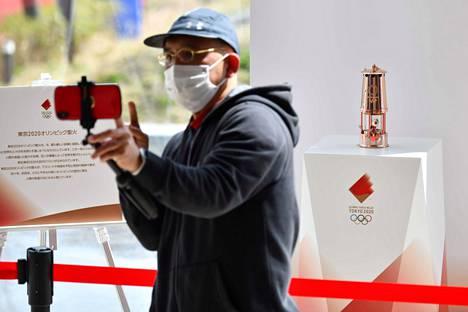 Mies otti kuvaa itsestään olympiatuli taustallaan Narahan kaupungissa torstaina. Olympialaisten piti alkaa Tokiossa 24. heinäkuuta, mutta kisoja on lykätty vuodella eteenpäin.