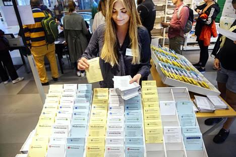 Vaalityöläinen Frida Zetterlung asetteli vaalilipukkeita telineeseen ennakkoäänestyksen ollessa käynnissä Tukholmassa Nacka Forumin ostoskeskuksen kirjastossa.