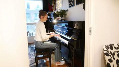 Aida Helimäki soittaa pianoa huoneessa, joka on äänieristetty sekä seinistä, lattiasta että katosta.