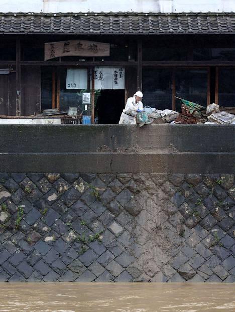 Asukas kaatamassa ämpärillisen mutaa jokeen puhdistaessa rakennusta tulvien jälkeen Ashikitan alueella Kumamoton prefektuurissa.