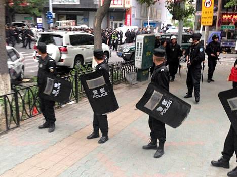 Mellakkapoliisit vartioivat pommi-iskupaikan lähellä Ürümqissa.