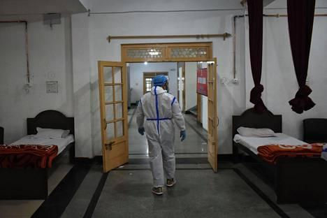 Terveydenhuollon työntekijä tarkistaa tiloja koronavirusepidemian takia sairaalaksi muutetussa rakennuksessa Srinagarissa. Sairaaloiden kantokyky Intiassa on äärimmillään koronavirustartuntojen levitessä voimakkaasti.