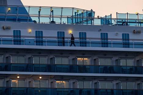 Hengitysmaskia pitävä aluksen työntekijä käveli karanteenissa olevan aluksen kannella maanantaina helmikuun 24. päivänä.