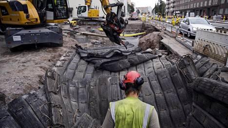 Arkadiankadun risteyksessä on ylimääräistä kalliota voitu jopa räjäyttää. Taustalla näkyy jätevesikaivo, josta asukkaitten jätevesiä pumpataan kaivannon ohi. PMM-Louhinnan Antti Fabribius poistaa irtokiviä räjäytysmattojen päältä.