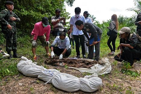 Pelastustyöntekijät tutkivat joukkohaudasta löytyneitä ihmisen jäänteitä Padang Besarin kylän lähistöllä Etelä-Thaimaassa keskiviikkona.