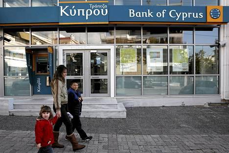 Nainen lapsineen ohitti Bank of Cyprus -pankin konttorin Ateenassa.