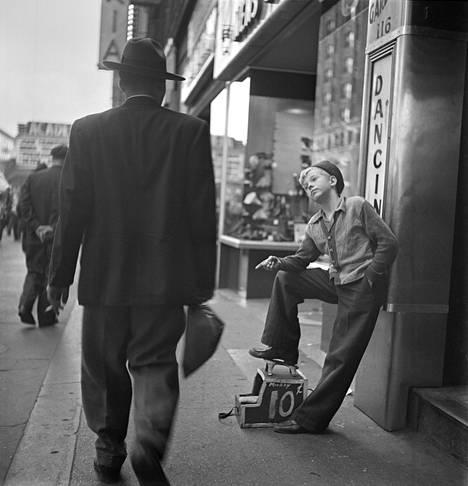 """""""Kengänkiillottaja"""", Julkaisematon, Arkistoitu: 6.10.1947. Kubrick otti yli 250 valokuvaa seuratessaan kengänkiillottajapoika Mickeyn päivää. Mickeytä ja tämän sisarusparvea kuvaamalla Kubrick näytti, kuinka poika teki kovasti töitä auttaakseen perheensä elättämisessä."""