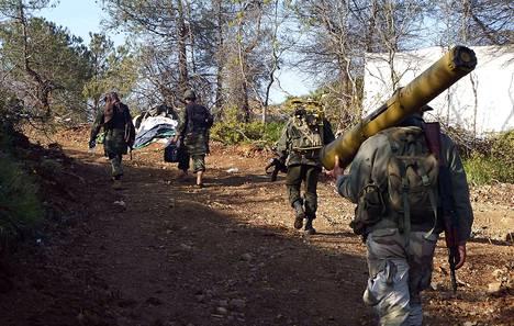 Hallitusta vastustava kapinallinen kantoi panssarinyrkkiä kulkiessaan kohti asemia lähellä Kasabia keskiviikkona.
