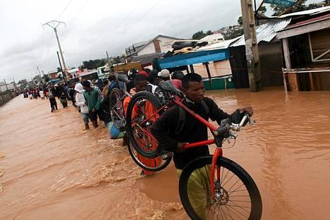 Paikalliset asukkaat kulkivat tulvivaa katua pitkin Sabotsy Namehanassa Antananarivosta pohjoispuolella tiistaina.