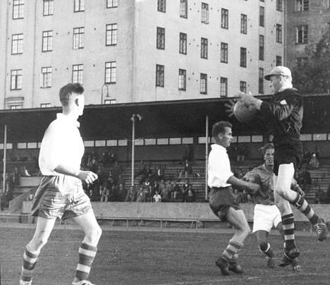 Helsingin Toverien maalivahti Pertti Rignell ottaa kiinni Karhulan Peli-Karhujen pelaajan ampuman pallon. Kuva on julkaistu Helsingin Sanomissa heinäkuussa 1959.
