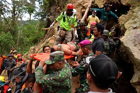 Pelastustyöntekijät kantoivat romahtaneesta kaivoksesta pelastettua miestä Bolaang Mongondowissa Indonesiassa tiistaina.