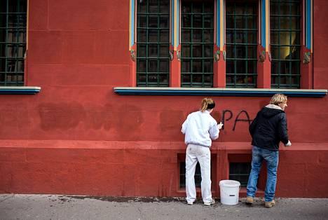 Lucie Mahner ja hänen isänsä Gregor Mahner pesivät maahanmuuton rajoituksia vastustavaa iskulausetta Baselin punaisen raatihuoneen seinästä tiistaina.