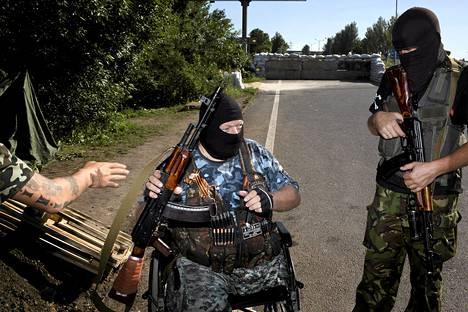 Venäläismielisten separatistien asemiehiä tiesululla Donetskin ulkopuolella.