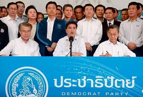 Demokraattisen puolueen johtaja Abhisit Vejjajiva (keskellä) kertoi puolueen vaaliboikotista Bangkokissa lauantaina.