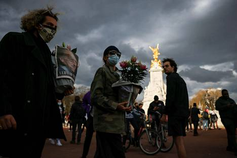 Ihmisiä Victoria Memorial -veistoksen luona Lontoossa perjantaina.