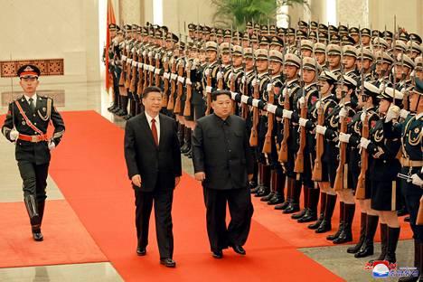 Pohjois-Korean johtaja Kim Jong-un ja Kiinan presidentti Xi Jinping tarkastavat kunniavartion Pohjois-Korean julkaisemassa kuvassa.