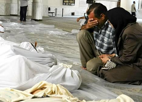 Syyrian opposition julkaisemassa kuvassa syyrialainen pariskunta suree käärittyjen ruumiiden äärellä.