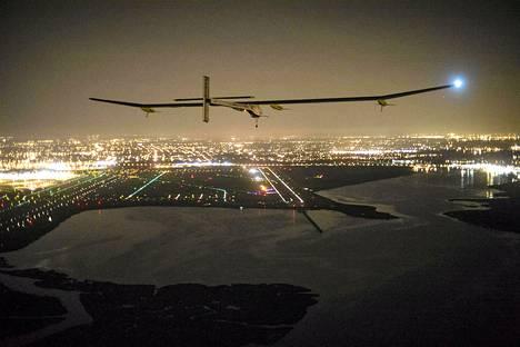 Aurinkovoimalla toimiva Solar Impulse HB-SIA -lentokone laskeutumassa John F. Kennedyn lentokentälle New Yorkiin myöhään lauantaina.
