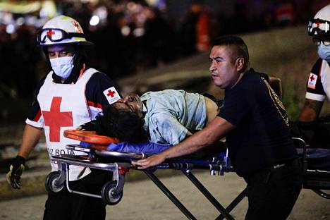 Pelastustyöntekijöitä kuljettamassa onnettomuudessa loukkaantunutta.