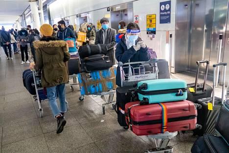 Matkustajat jonottivat turvatarkastukseen Heathrow'n lentokentällä Lontoossa 21. joulukuuta. Matkustajaliikenne Britanniasta moniin muihin Euroopan maihin keskeytettiin samoihin aikoihin uuden koronavirusmuunnoksen leviämisen ehkäisemiseksi.