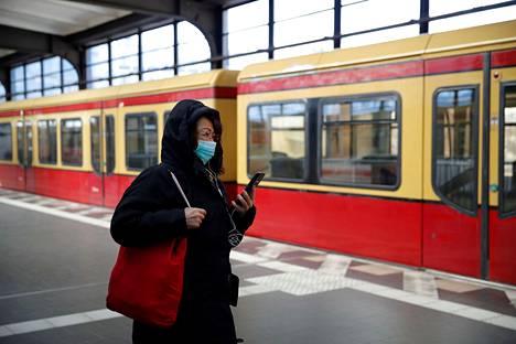 Matkustaja kulki Berliinin Zoologischer Gartenin asemalla älypuhelimen ja kasvosuojaimen kanssa huhtikuun 21. päivä.