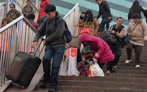 Matkustajat kiirehtivät junaan Pekingin rautatieasemalla keskiviikkona. Useimmilla kiinalaisilla on uudenvuoden aikaan lomaa, ja juhlaa vietetään perheen kanssa. Se merkitsee valtavia ruuhkia, sillä sadat miljoonat kiinalaiset työskentelevät muualla kuin kotiseudullaan.