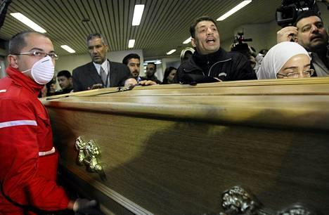 Punaisen ristin työntekijä kantaa Syyriassa kuolleen valokuvaajan Remi Ochlikin arkkua.