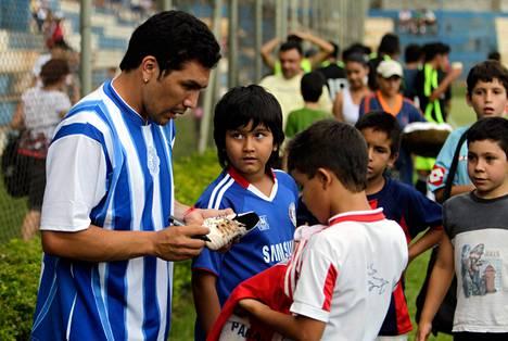 Salvador Cabanas jakeli nimikirjoituksia lapsille valmistautuessaan toissapäivänä paluuotteluunsa Asuncionissa.