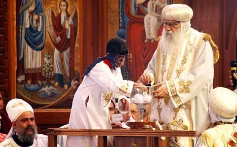 Kuoripoika Bishoy Girgis Masaad nosti ehtoollismaljasta uuden koptipaavin nimen sisältäneen lipukkeen Pyhän Markuksen katedraalissa Kairossa sunnuntaina.