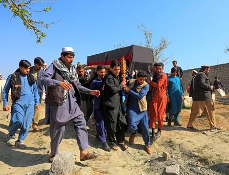 Miehet kantoivat ammutun naistoimittajan ruumisarkkua Jalalabadissa maaliskuun alussa.