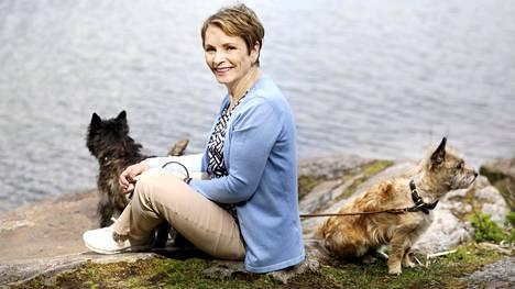 Marja Aarnipuro rentoutuu lenkkeilemällä kahden cairnterrierinsä Veeran ja Petrin kanssa.