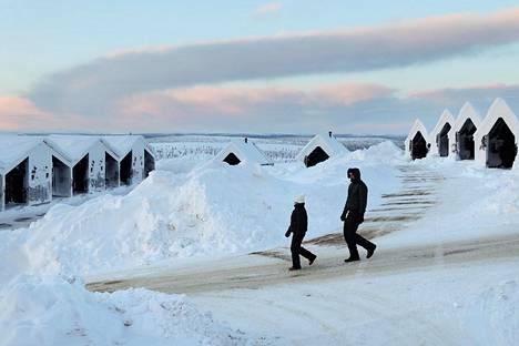 Koronaviruksen vaikutukset ovat näkyneet etenkin matkailualalla, joka on kärsinyt epidemian vuoksi asetetuista rajoituksista. Kuvassa on kaksi turistia Star Arctic Hotellin pihalla Saariselällä.
