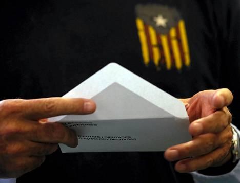 Itsenäisyysmielisten tähtilipputunnusta paidassaan kantanut mies sulki äänestyskuoren Barcelonassa Katalonian aluevaaleissa sunnuntaina.