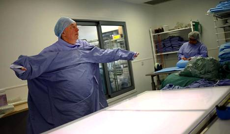 Pesulatyöntekijä suoristi pestyä hoitaja-asua sairaalan pesulassa.