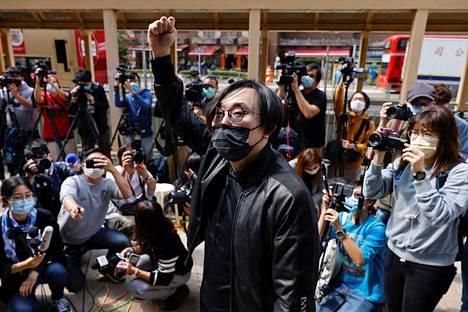 Demokratia-aktivisti Mike Lam King-nam tervehti tiedotusvälineitä saapuessaan ilmoittautumaan poliisiasemalle syytteiden vuoksi sunnuntaina Hongkongissa.