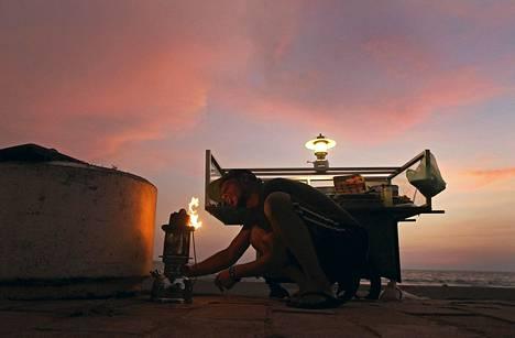 Myyjä sytytti kerosiinilampun kojunsa vieressä yötorilla Colombossa Sri Lankassa. Sri Lanka aikoo nostaa sähkön hintaa huhtikuussa. Valtio-omisteisten yhtiöiden dieselin ja bensan hintoja on jo nostettu.