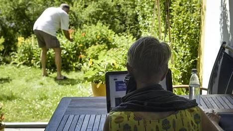 Mies puuhasteli puutarhassa, kun nainen teki etätöitä kotitoimiston terassilla Vantaalla viime kesänä.