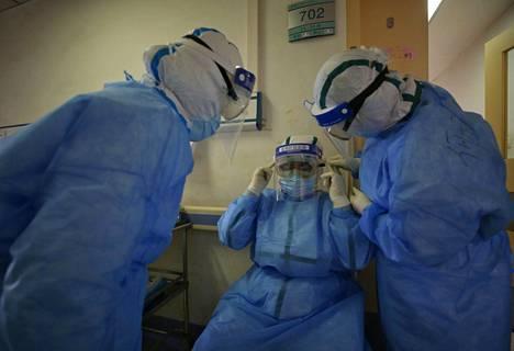 Sairaalan henkilökunta pukeutui huolellisesti suojavarusteisiin wuhanilaisessa sairaalassa maanantaina.