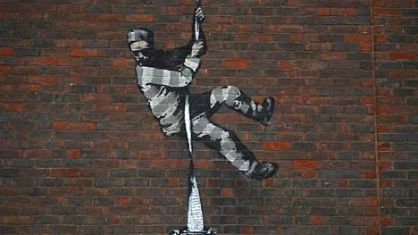 (FILES) This file photo taken on March 02, 2021 shows an artwork by street artist Banksy on the side of Reading Prison in Reading, west of London. - Street artist Banksy on March 4 claimed responsibility for a painting on the wall of a former British prison that once held playwright Oscar Wilde. The artwork shows a prisoner escaping on a rope made of bedsheets tied to a typewriter. LEHTIKUVA / AFP Instructions: RESTRICTED TO EDITORIAL USE - MANDATORY MENTION OF THE ARTIST UPON PUBLICATION - TO ILLUSTRATE THE EVENT AS SPECIFIED IN THE CAPTION