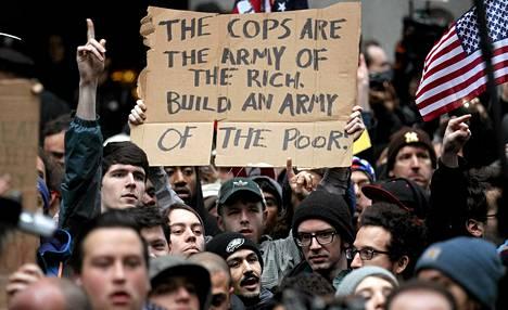 Kyltin teksti: Poliisi on rikkaiden armeija. Muodostakaa köyhien armeija.
