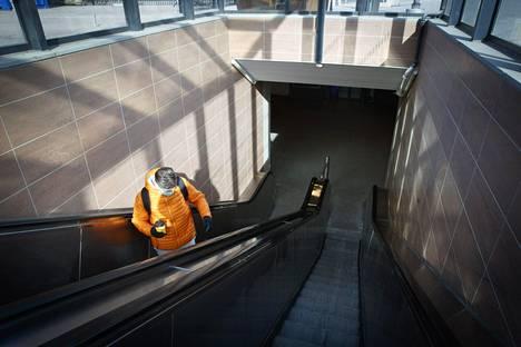 Yksinäinen matkailija Tampereen hiljentyneellä rautatieasemalla sunnuntaina.