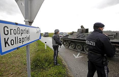 Poliisit seisovat panssariajoneuvojen vieressä Grossprieliin johtavalla tiellä. Tie johtaa maalaistaloon, jonne salametsästäjä on sulkeutunut.