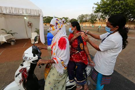 Nainen saa rokotteen skootterin kyydissä Madhya Pradeshin osavaltiossa toukokuun lopussa.