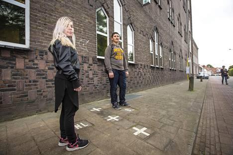 Elise van Meer seisoo Hollannin Baarle-Nassaussa, kun hänen kaverinsa Renis Muca seisoo Belgian puoleisessa Baarle-Hertogissa.