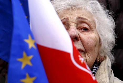 Nainen heilutti EU:n ja Puolan lippuja hallituksenvastaisessa mielenosoituksessa Varsovassa lauantaina.